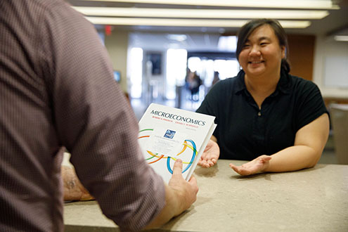A student being given a textbook through the Top Textbooks program.