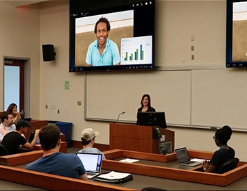 A professor using video conferencing to remotely lecture for a class.