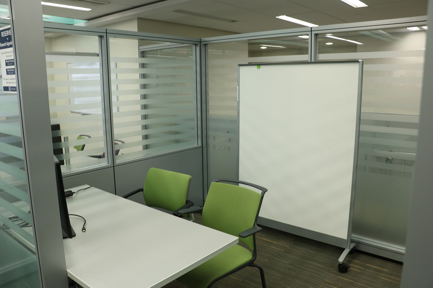 View of whiteboard, 2 chairs (moveable), computer