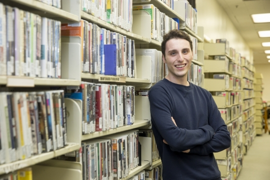 Student standing in the Gelman stacks